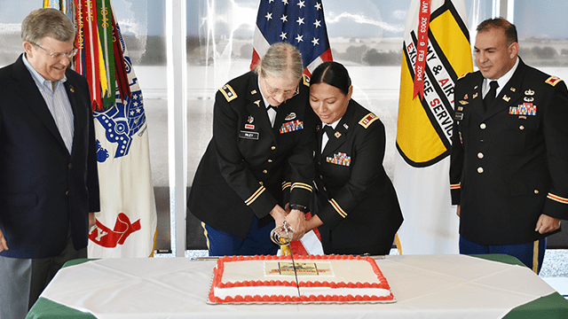 Lt. Col. Patricia Riley, staff veterinarian (center, left), and Cpt. Lucia Tartt, transportation officer (center, right), cut a cake during a ceremony celebrating the U.S. Army's 243rd birthday at the Exchange's Dallas HQ. To observe Army tradition, the youngest and oldest Soldiers in the command have the honor of cutting the cake. Director/CEO and Army Veteran Tom Shull, Exchange director/CEO and an Army veteran, left, and Army Col. Juan Saldivar, the Exchange's command engineer, right), spoke at the ceremony.      SFC Tim Meyer
