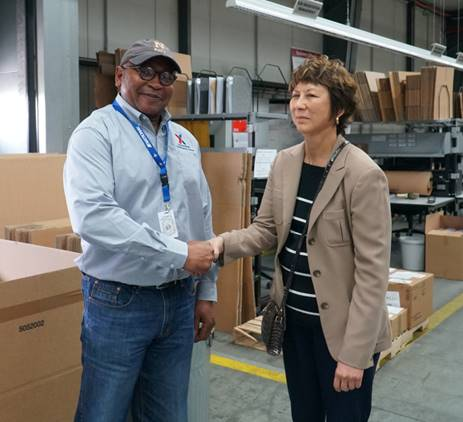 Roger Wright,  business-to-business foreman at Germersheim, receives a coin from Executive Vice President and Chief Logistics Officer Karen Stack for his work getting the B2B operations running.
