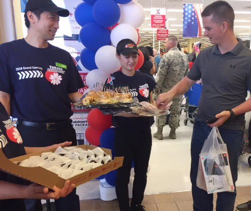 The food court's Satoshi Hada and Asuka Horiguschi hand out samples of food during the grand re-opening of the Yokota AB Exchange.