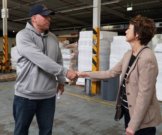 Shipping Foreman Omar Almanzar is greeted by Executive Vice President and Chief Logistics Officer Karen Stack.
