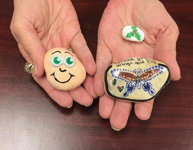 Hands holding 3 rocks.