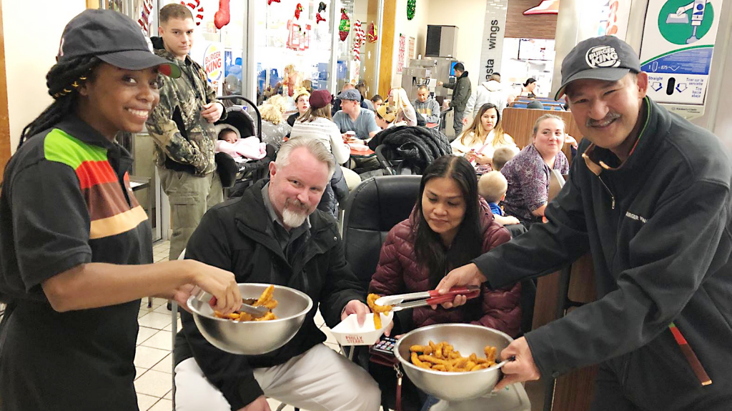 MISAWA AB, Japan - Burger King associates Jayla Wood and Freddie Figuracion hand out samples of Chicken Fries to hungry participants during the food court's big Bingo night.