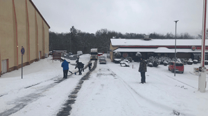 BAUMHOLDER, Germany - No amount of cold, wintery weather can freeze the spirit of family serving family! Associates from Baumholder's Military Clothing Store and Burger King clear a path for an Exchange trucker on the whopper of a snowy hill.