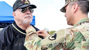 Vietnam Vet getting lapel pin from installation commander.