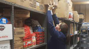 Store Manager Katie Oster moves products to a top shelf out of harm's way.