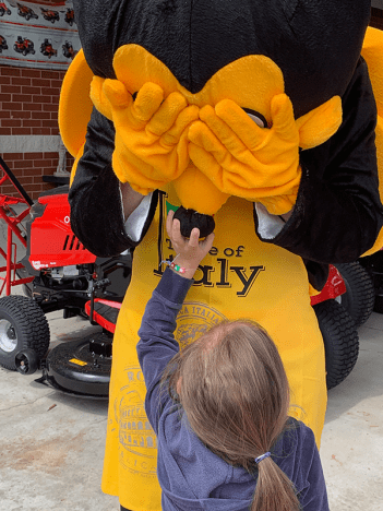 FORT LEE, Va. - A little girl squeezes the nose of the Exchange safety bee mascot during the grand opening of the store's outdoor living center. Playing the mascot was Loss Prevention's Cooper Stegmann.