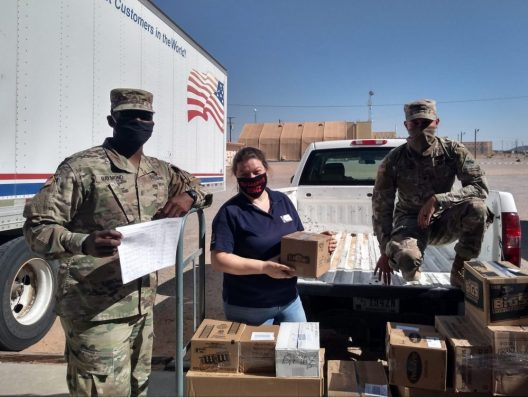 Sgt. Tehjmar Raymond (left) and Spc. Nathaniel Causley (right) help McGregor Field Troop Store Manager Tina Bretz load orders placed through the Fort Bliss Exchange's personal shopper program onto a truck to be transported to quarantined Soldiers at Fort Bliss.