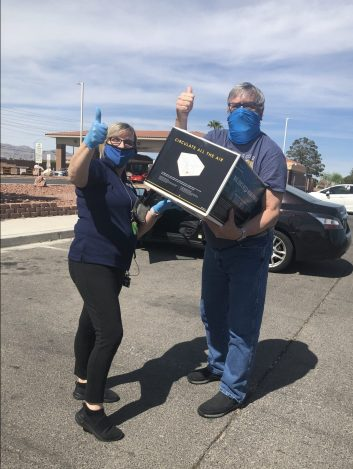 From left, Nellis Air Force Base Exchange Customer Service Supervisor Gisela Jameson meets shopper Daniel Borkowski in the parking lot of the base's visitor's center to deliver his buy online, pickup in store order.