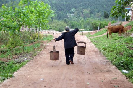 A person carrying farm implements on a rural road