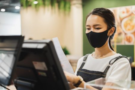 Asian staff restaurant waitress wear protective face mask working in the restaurant with social distancing to protect infection from coronavirus covid-19