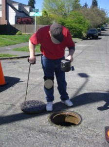 Don Pace, of the Solid Waste, Rodents and Zoonotics Program, examines a sewer for rats