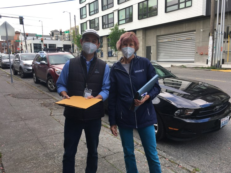 Man and woman standing outside holding binders and papers