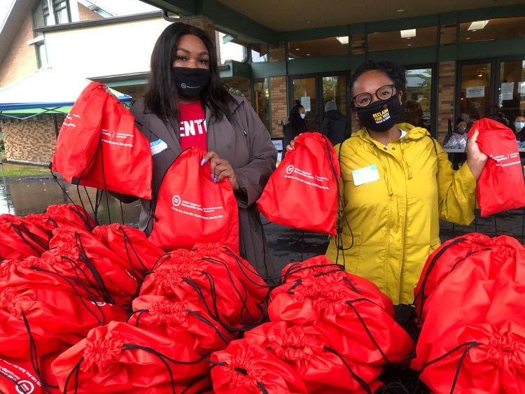 Two staff and volunteer members with the Urban League of Metropolitan Seattle wearing masks are holding several red backpacks with resources to support with pandemic recovery.