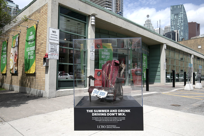A Muskoka chair placed in a glass case with text 'The summer and drunk driving don't mix'