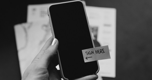 Black and white image of mobile phone with a sticker that says 'sign here' on it.