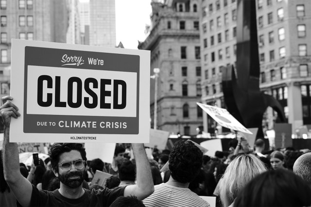 """black and white image of a climate march with a person holding up a sign saying """"sorry, we're closed due to climate crisis."""""""