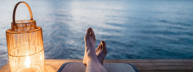 Feet relaxing on a dock in front of a lake with a lantern by the side