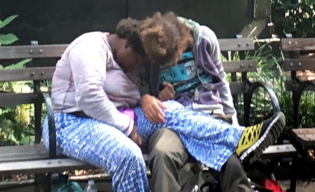 Two people huddled on a bench