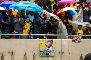 South Africans protect themselves from the rain at the memorial service for Nelson Mandela. © Chuck Kennedy | WhiteHouse.gov