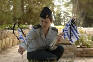 An IDF officer places new Israeli flags on the graves of IDF soldiers. © Israeli Defense Forces | Flickr