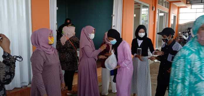 Istri Kepala Desa Cicadas Maryamah membagikan paket sembako pada, Minggu (11/04/2021)