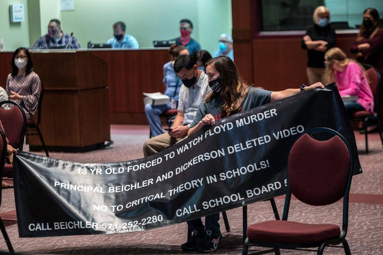 A woman holds up her sign against Critical Race Theory (CRT) being taught during a Loudoun County Public Schools (LCPS) board meeting in Ashburn, Virginia, on Oct. 12. The Loudoun county school board has clashed with parents over transgender issues, the teaching of CRT and COVID-19 mandates. Recently tensions between parents and the school board increased after parents say a young male wearing a dress sexually assaulted a girl in a school restroom.