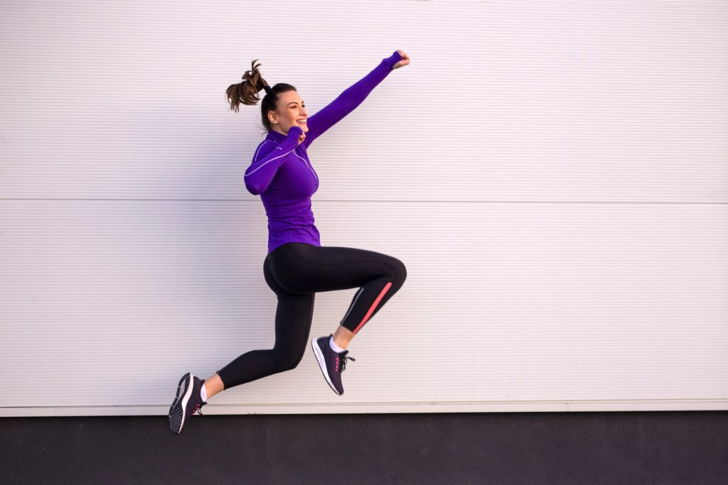 Young woman exercise and jump on street with white background