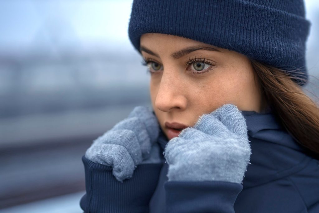 Beautiful face of green eyed fitness woman in winter skully hat and blue winter gloves holding jacket collar with hands. Close up portrait view