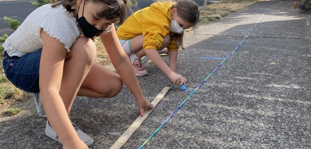 On a neighborhood sidewalk two fourth graders use a yardstick to measure a very long finger weaving