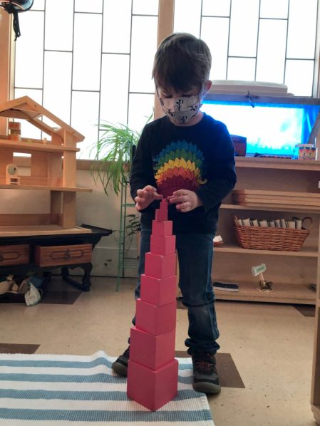 A young child carefully straightens the smallest cube atop a pink tower of cubes. Behind him is a wall of frosted windows and shelves with activities