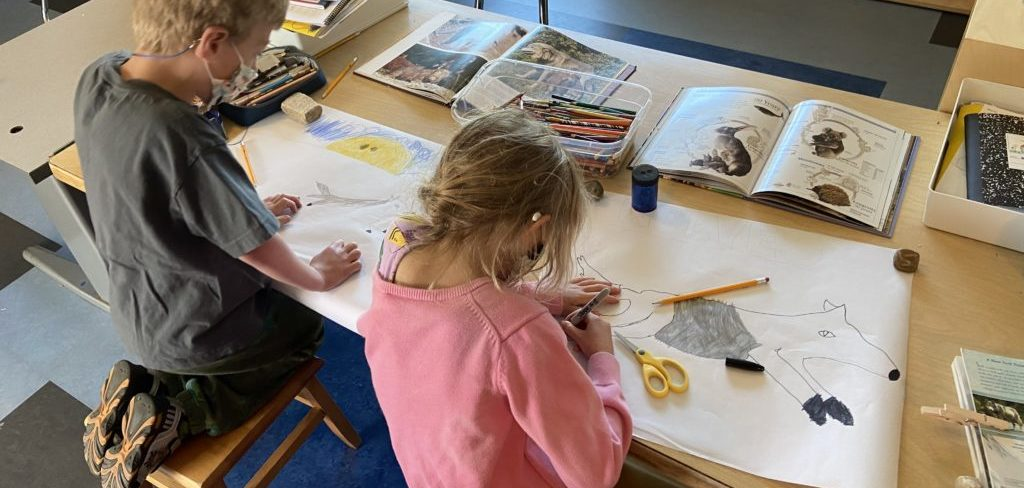 Two elementary aged children work side-by-side creating posters of ice age animals. Multiple books are spread open near them on the table.