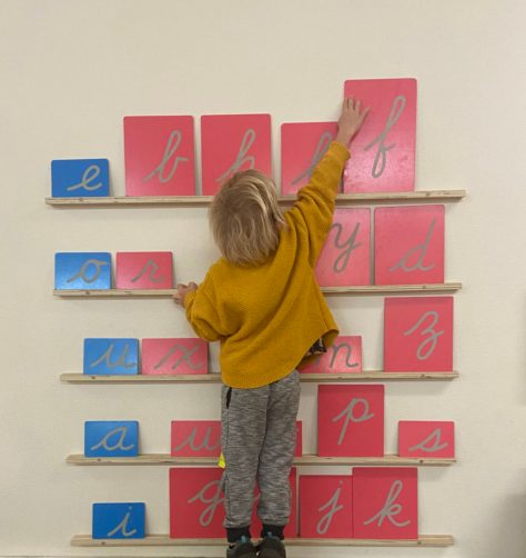 Pink and blue Sandpaper Letters are displayed on a wall. A 5 year old reaches for the one they want.