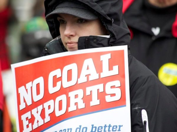 """A protester holds a sign saying """"No Coal Exports""""."""