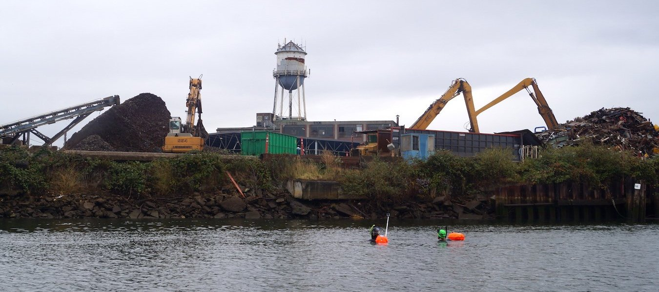 Katelyn Kinn and Mark Powell in the Duwamish River near Seattle Iron and Metals.