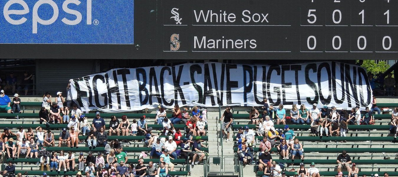 "A banner with the words ""Fight Back - Save Puget Sound"" is held up at a Mariners game."