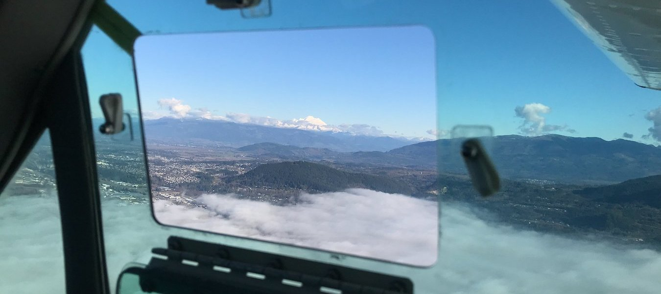 A view through the window of a plane shows mountains in the distance and fog over the landscape.