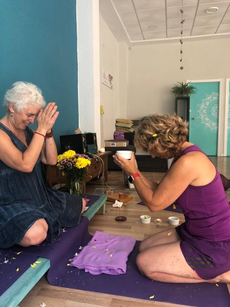 Alumna y profesora en la ceremonia de agradecimiento tras una formación de yoga