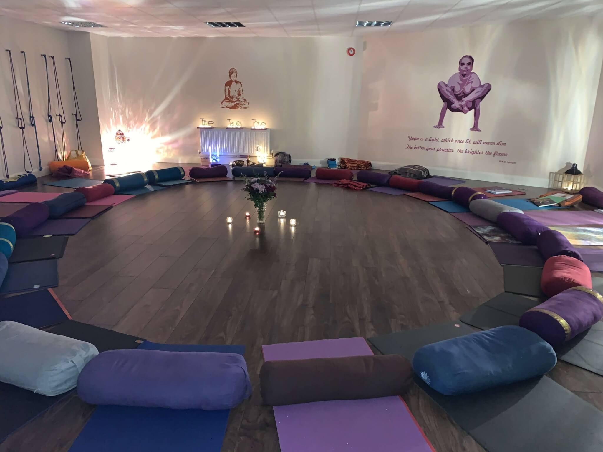Esterillas y cojines dispuestos en círculo preparados para dar una clase de yoga en una sala del Reino Unido
