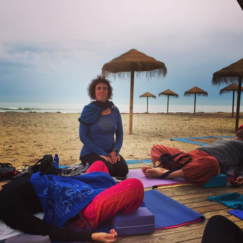 Profesora de yoga observa a varios alumnos acostados sobre cojines y esterillas con posturas de relajación de yoga en la playa de Puzol