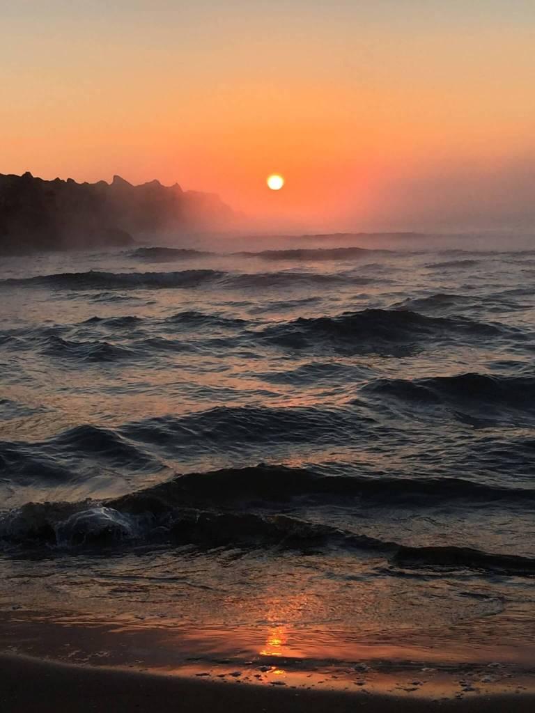 Salida del sol en la playa con bruma sobre el mar