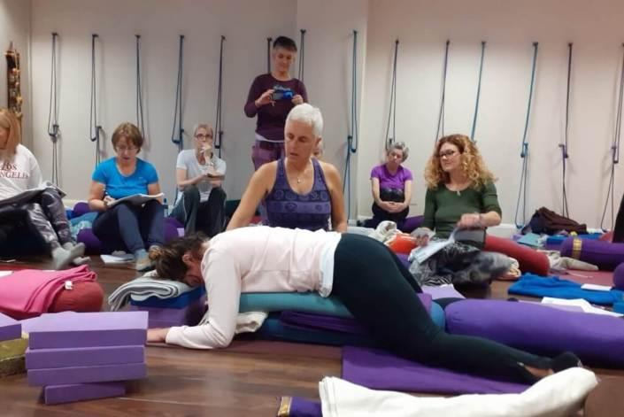 Postura boca abajo de una alumna asistida por la profesora de yoga restaurativo