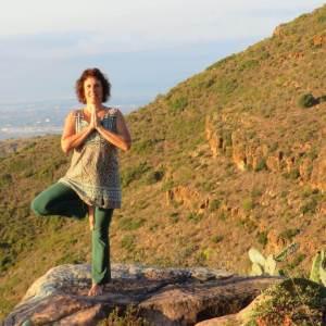 Sue Flamm sobre una roca en lo alto de una montaña en postura asana de arbol