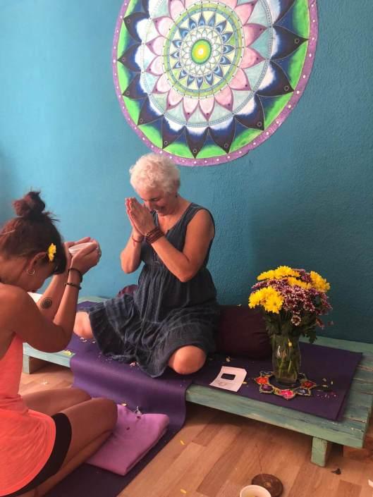 Sue Flamm en el altar de una sala de yoga agradeciendo la ofrenda de una alumna de yoga restaurativo