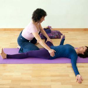 Sala de yoga donde la profesora ayuda con la postura con las manos en muslo y cadera de la alumna que está acostada boca arriba sobre la esterilla con una correa en el pie derecho y la mano derecha