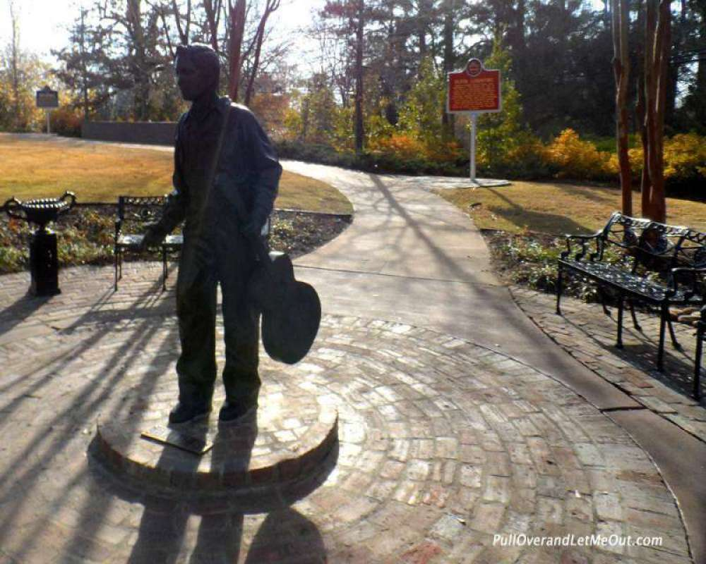A statue of young Elvis stands in the park.