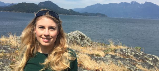 Poet Emily Osborne Standing in front of seascape with mountains in background