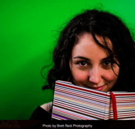 Author Erin Kirsh smiling behind book
