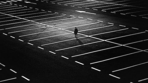 Man standing in dimly lit parking lot.