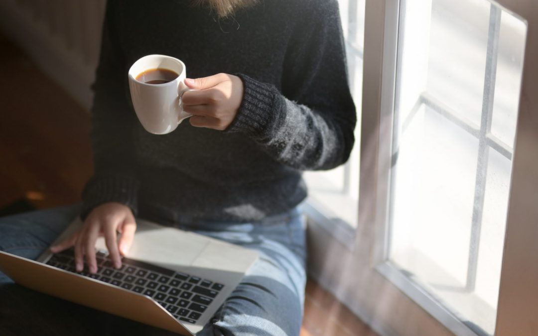 Woman using laptop while holding cup of coffee