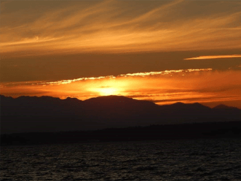 A photo of a golden sunset with mountains and water visible in the foreground.